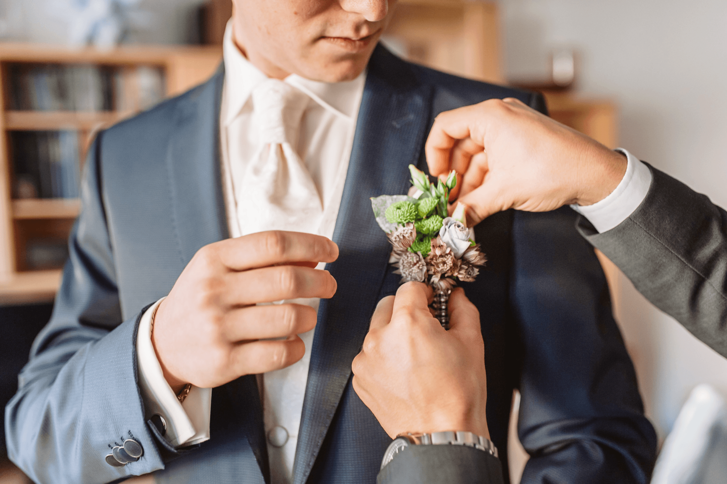 A groom having a flower arrangement attached to their pocket by a helper inside the groom suite at Paradise Banquet Halls.