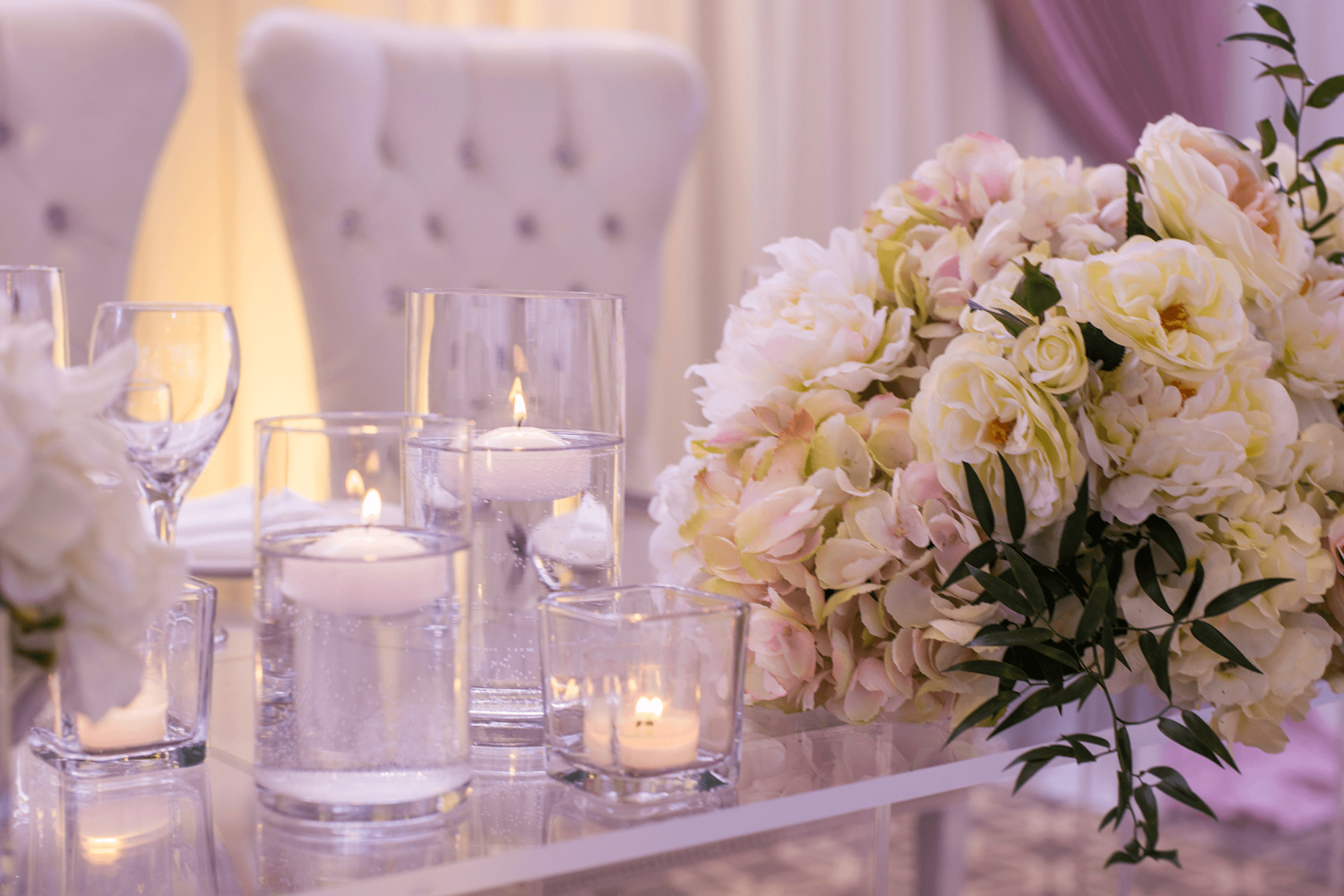 A close-up of a bouquet of flowers at the head table with candles and large, white chairs.