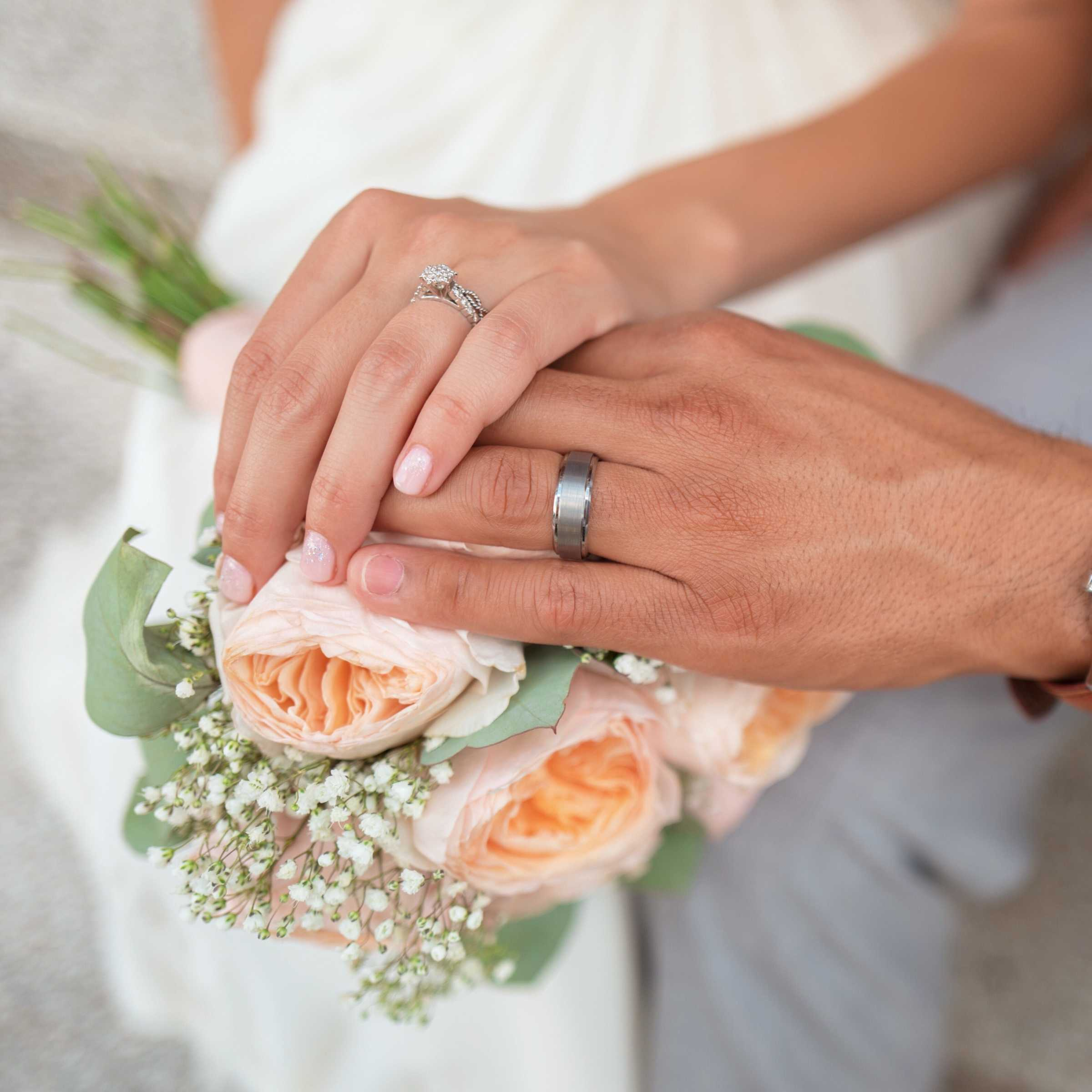 A wedding couple showing their rings over a bouquet of flowers.