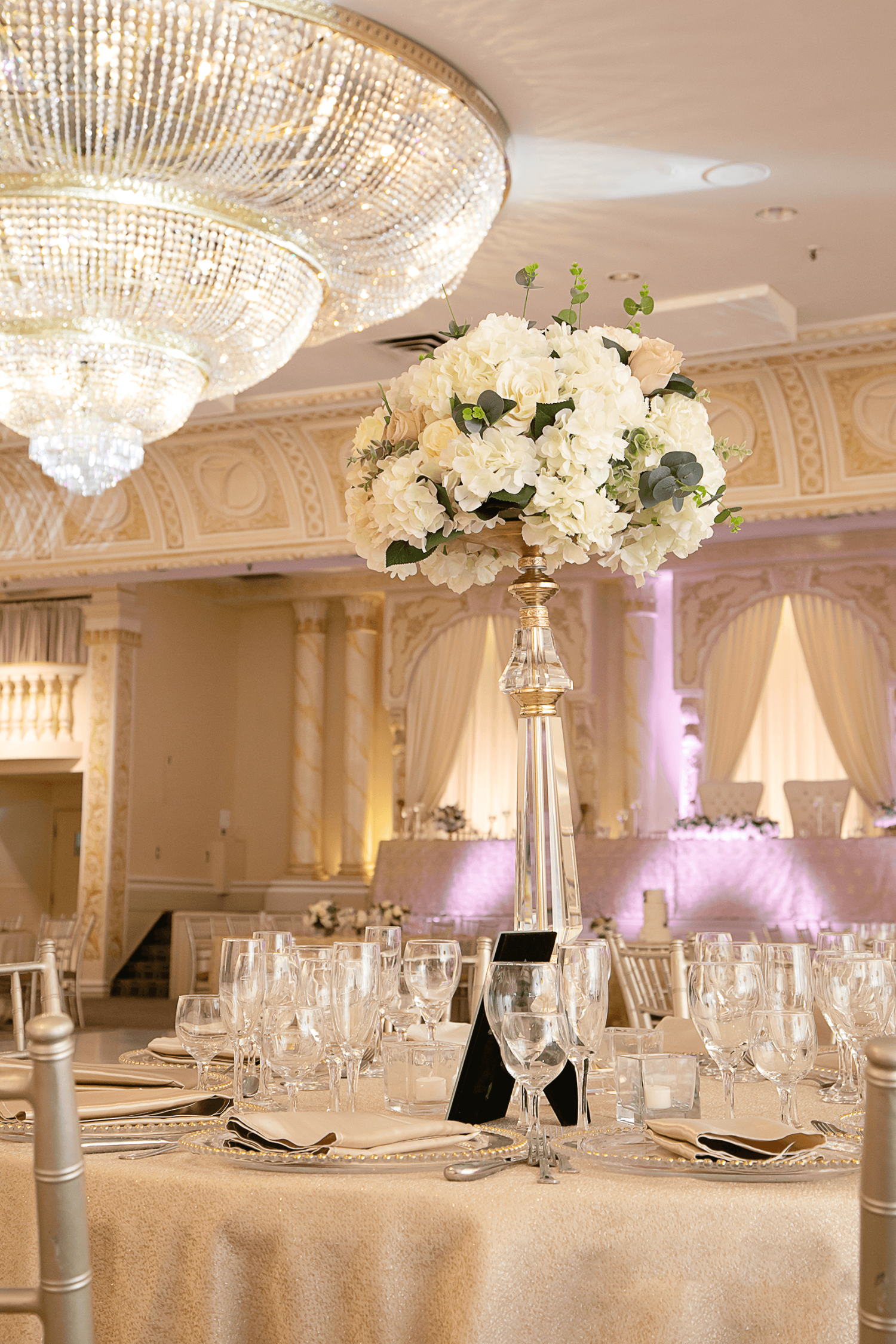A bouquet of flowers in a vase atop a table at a wedding with a huge chandelier at the Grand Queens Wedding Venue at Paradise Banquet Halls.