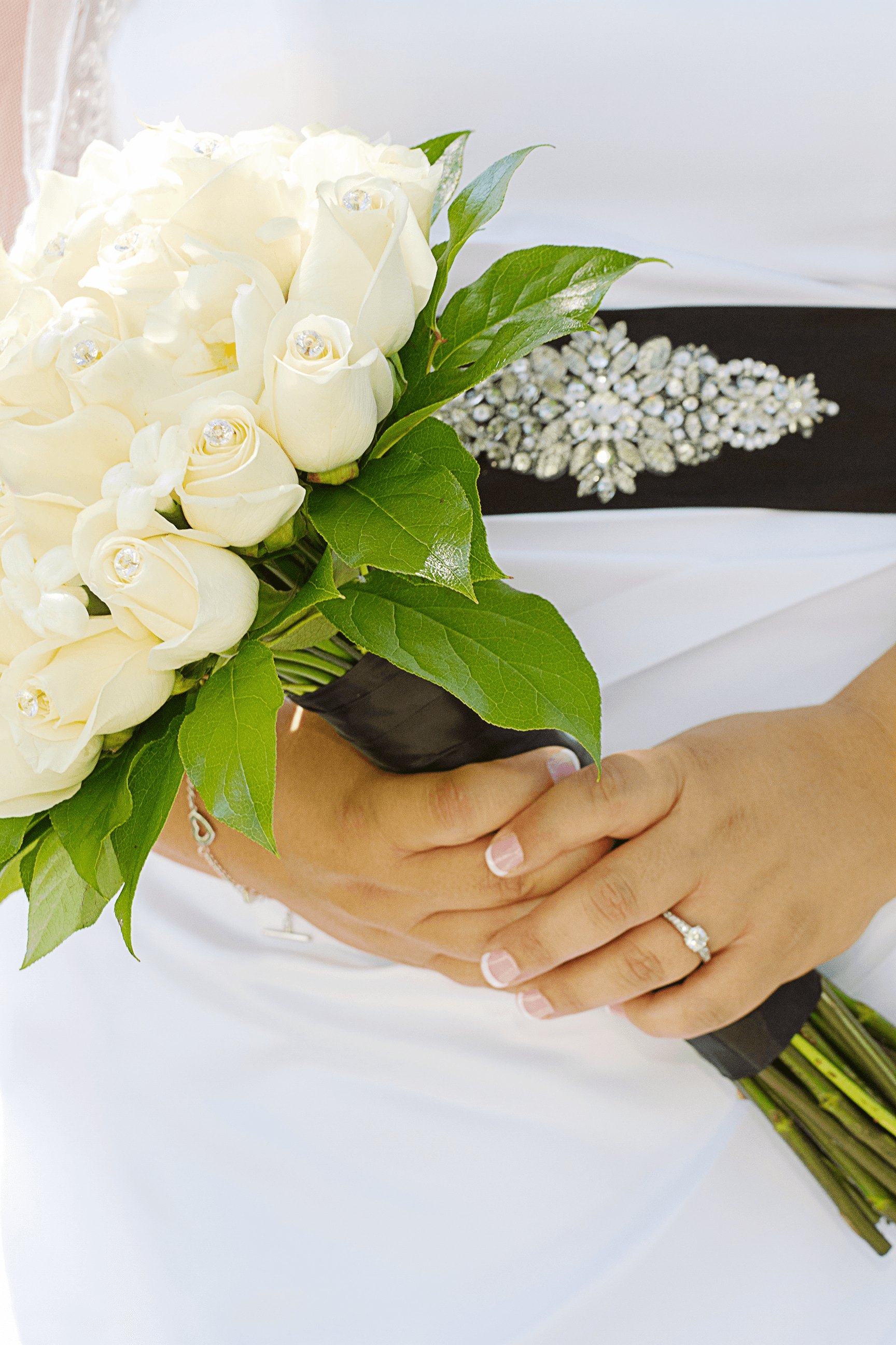 A bride with a bouquet of white roses and a wedding ring on their left hand.