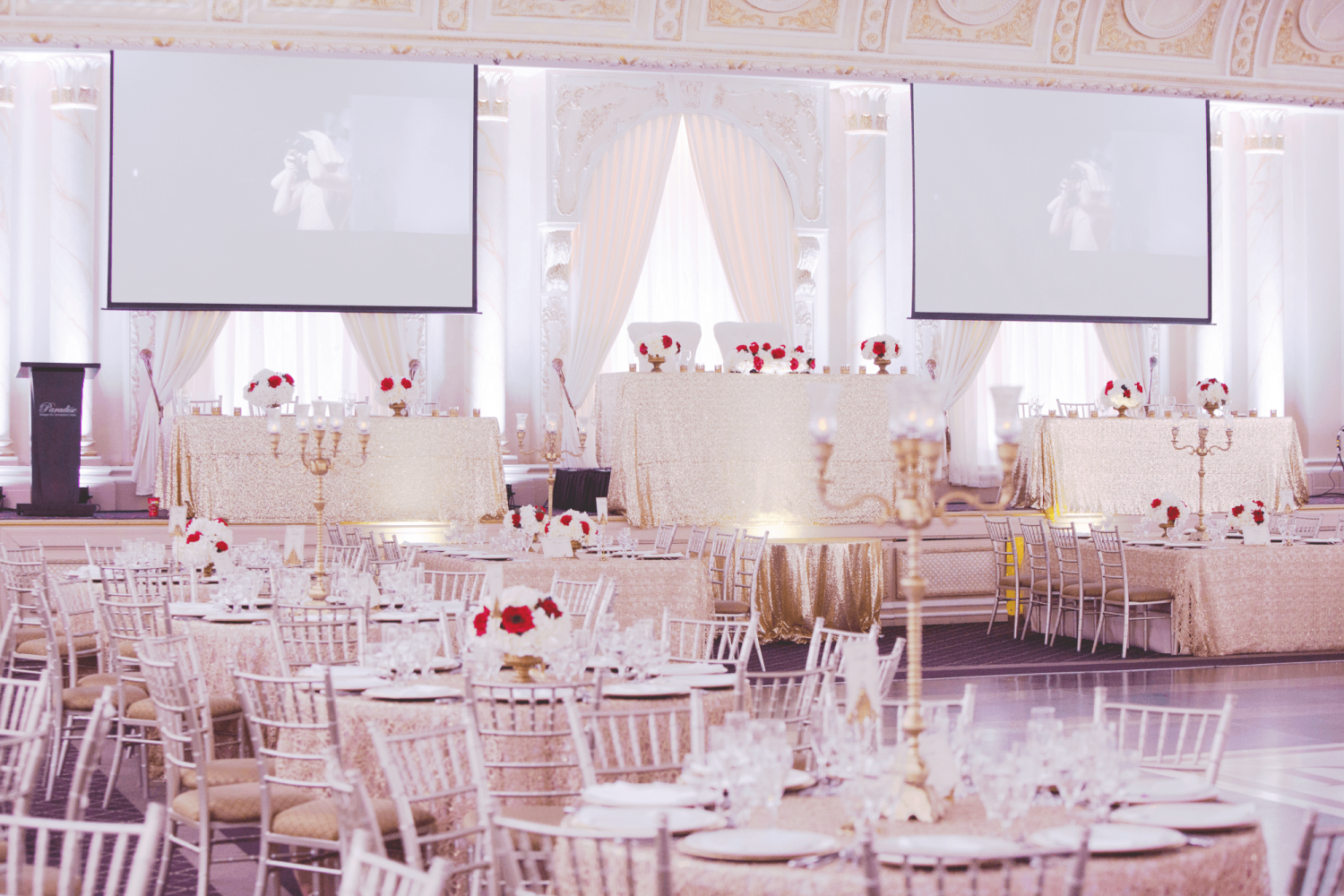 The Queen Mary Ballroom venue at Paradise Banquet Halls with a dance floor, circular tables with chairs, and a raised head table with a red and white flower colour scheme.