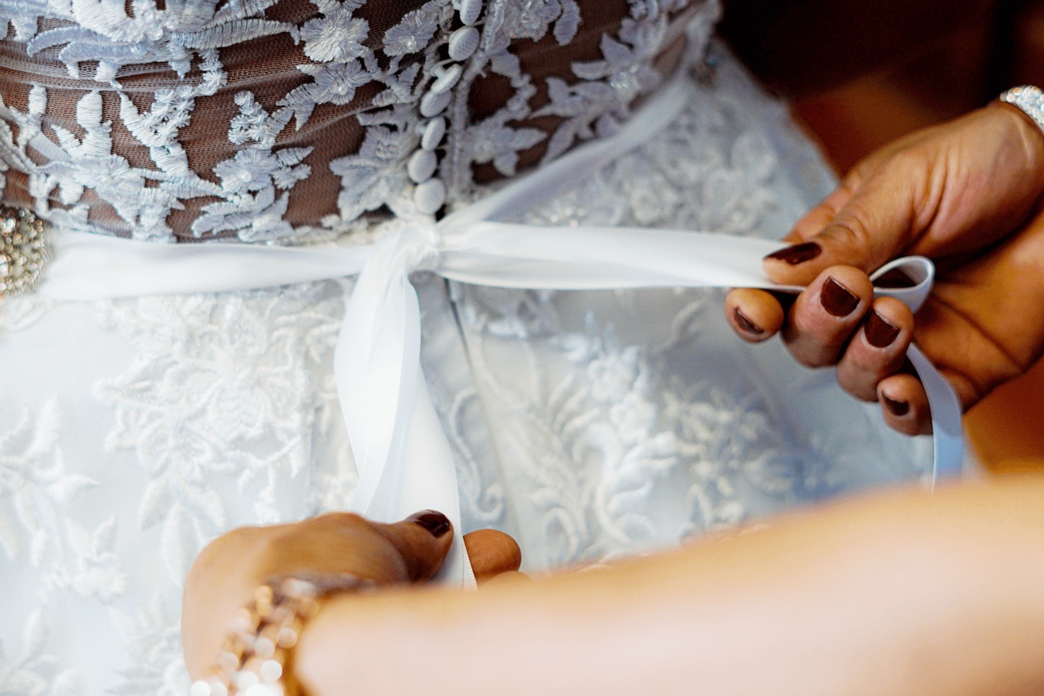 A bride is getting their waist tie tied by a helper inside the bridal suite of Paradise Banquet Halls.