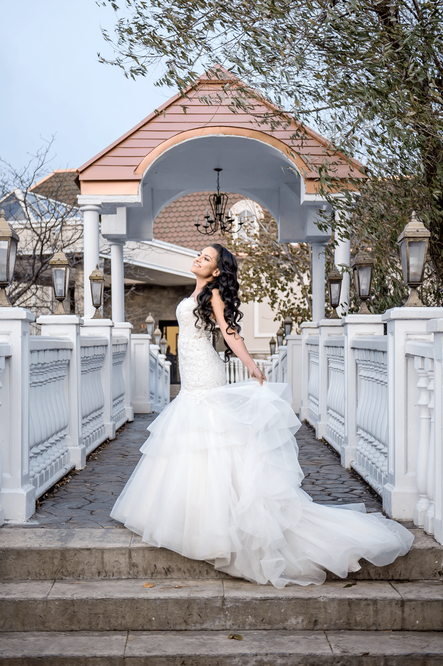 A bride in their wedding dress standing on a bridge with white railing outside at the Paradise Banquet Halls Garden Venue
