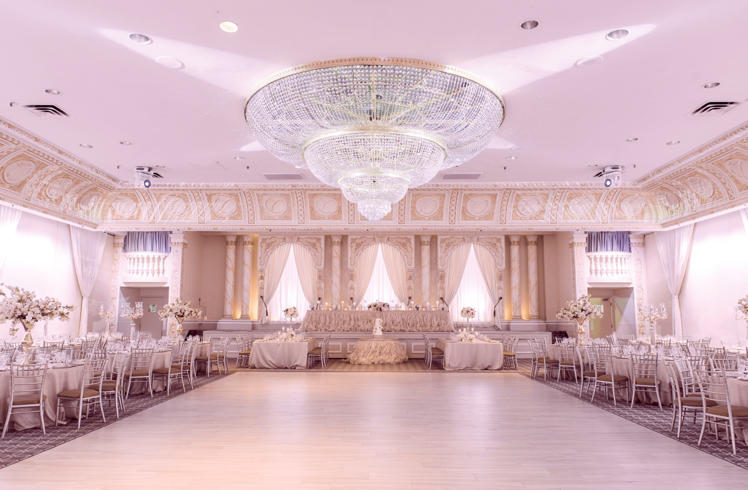 A wide shot of a ballroom with a dance floor and a chandelier.