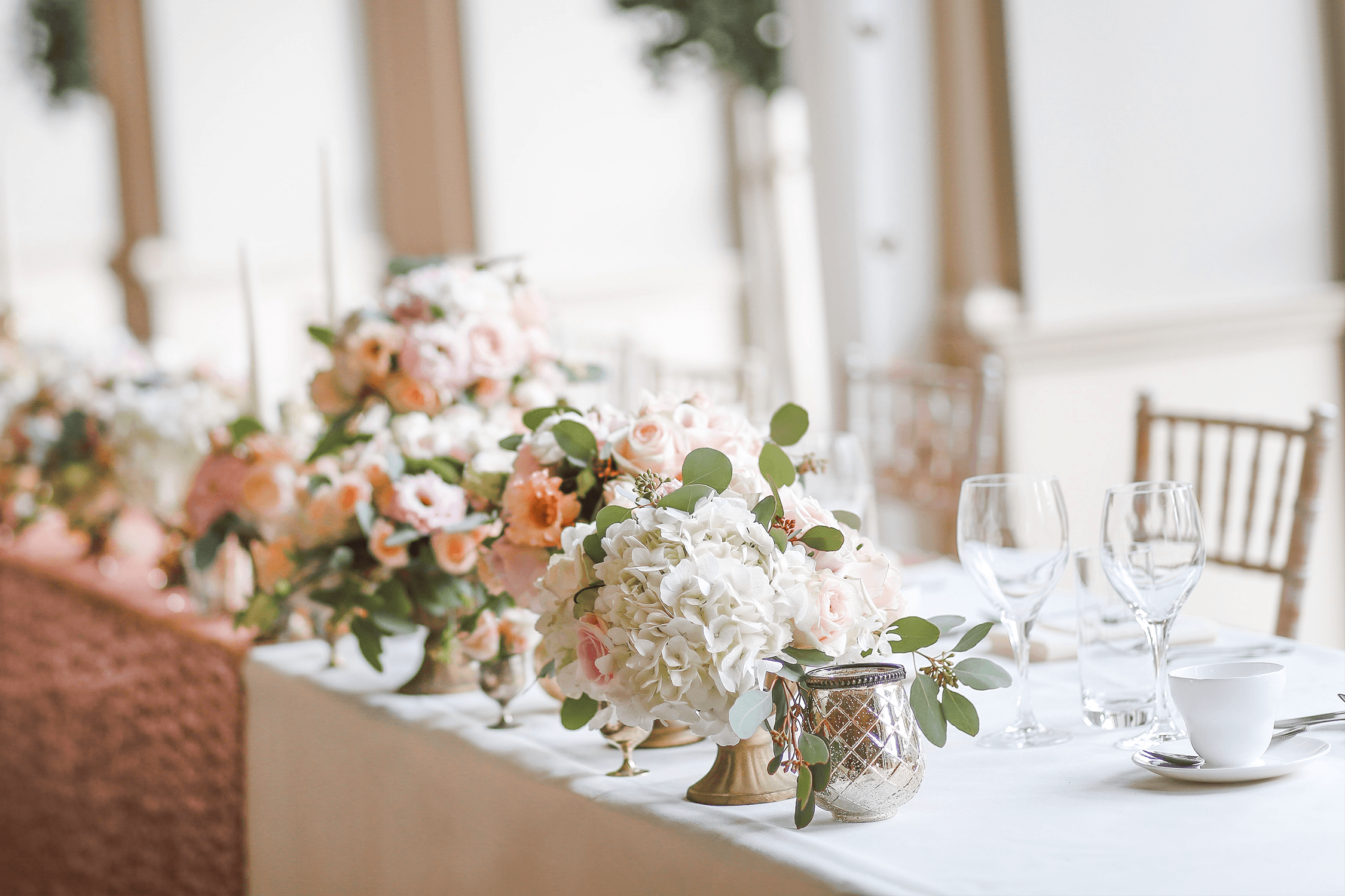 The head table at a wedding with white and pink flowers