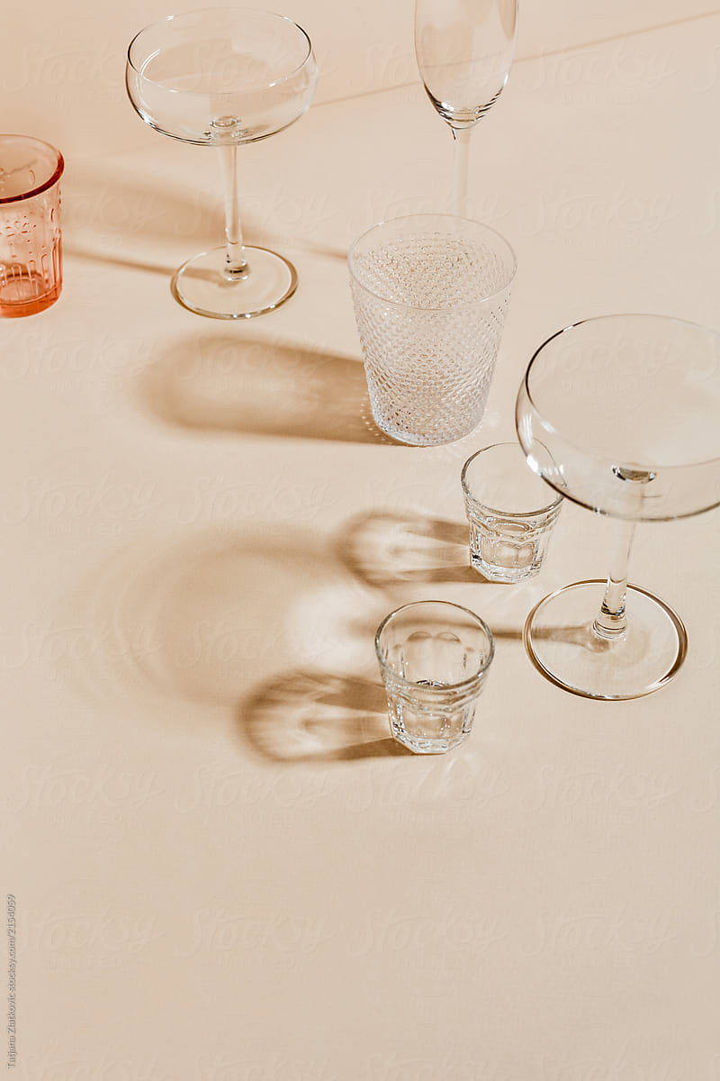 A loose collection of clear crystal glasses of various type with light passing through them onto a light, peach-coloured tabletop.