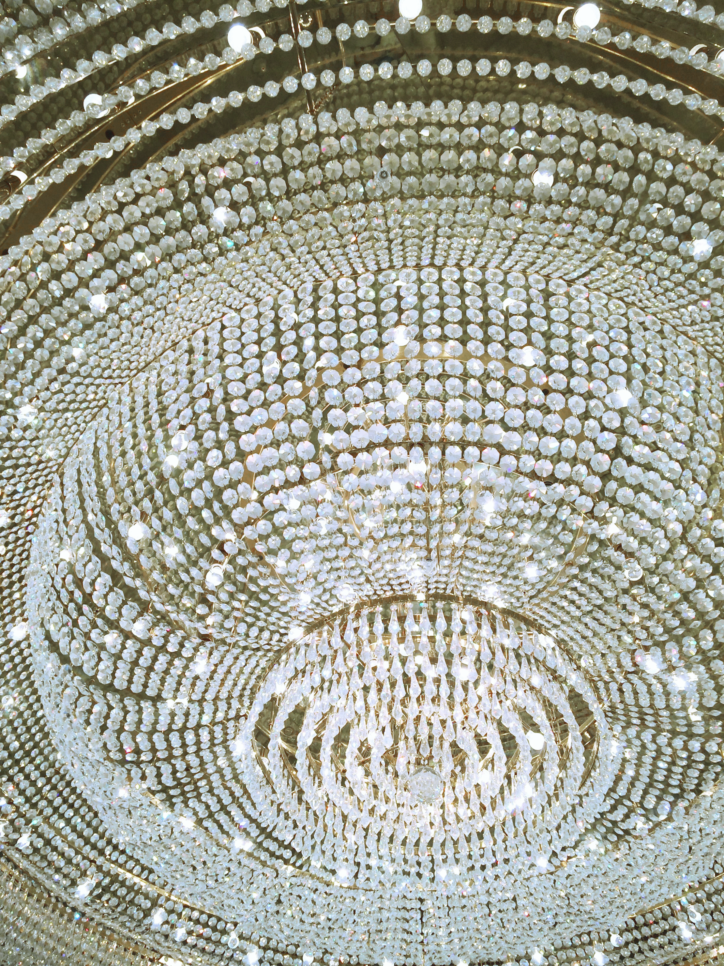 A close-up shot of a crystal chandelier from below.