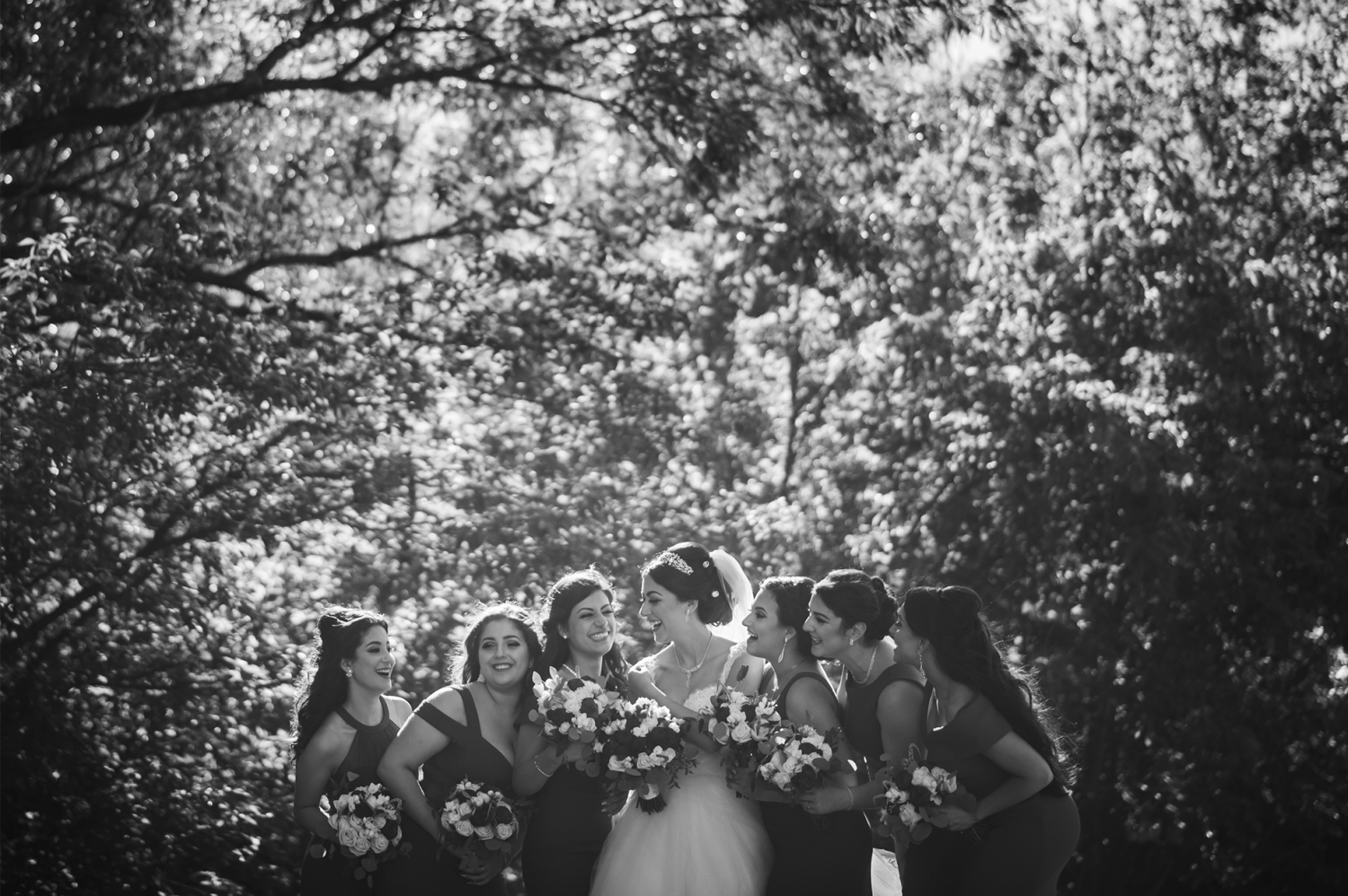 A bride and their bridesmaids grouped together outside in the Paradise Banquet Halls Garden venues.