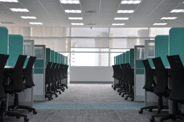An empty office with a dozen office chairs lined in cubicles.
