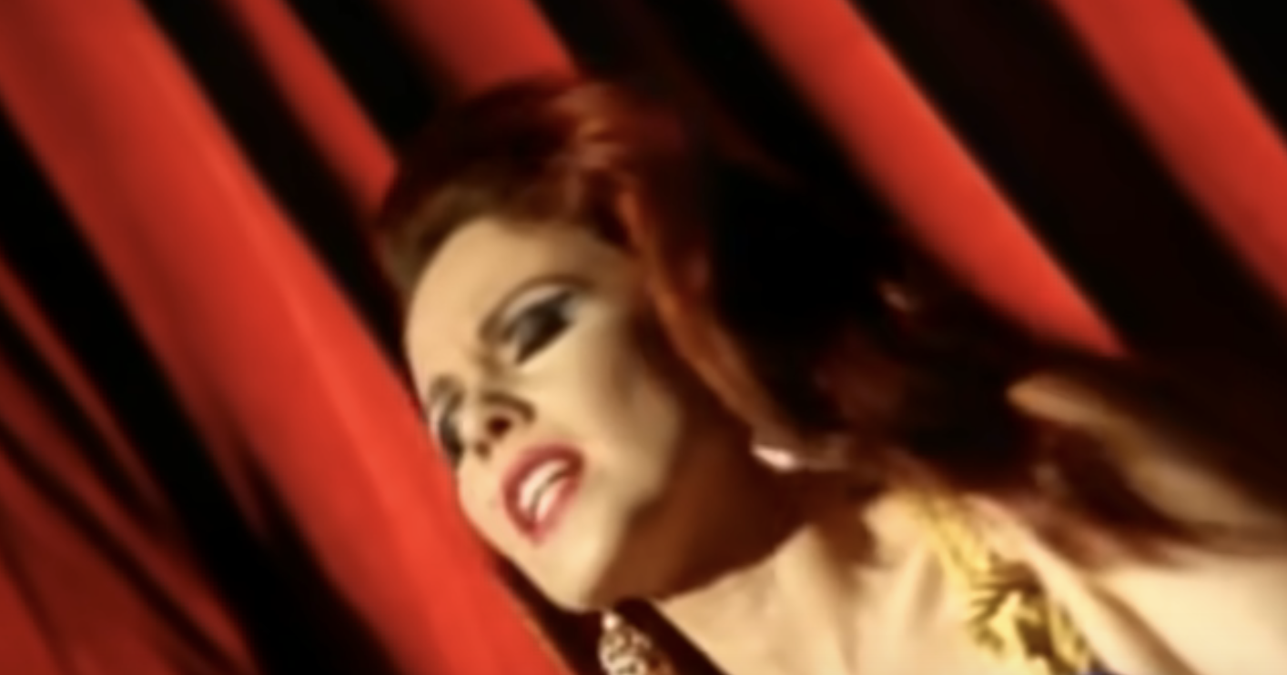 """Screenshot of the video """"Candy"""" from Iggy Pop showing a woman singing"""