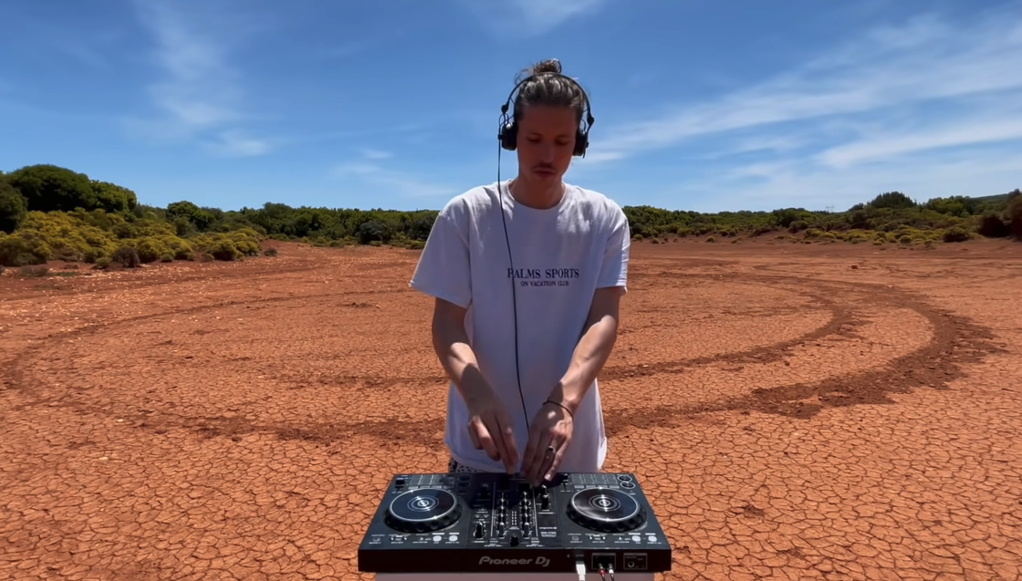 Chris Luno dj'ing in front of a background that looks like Mars