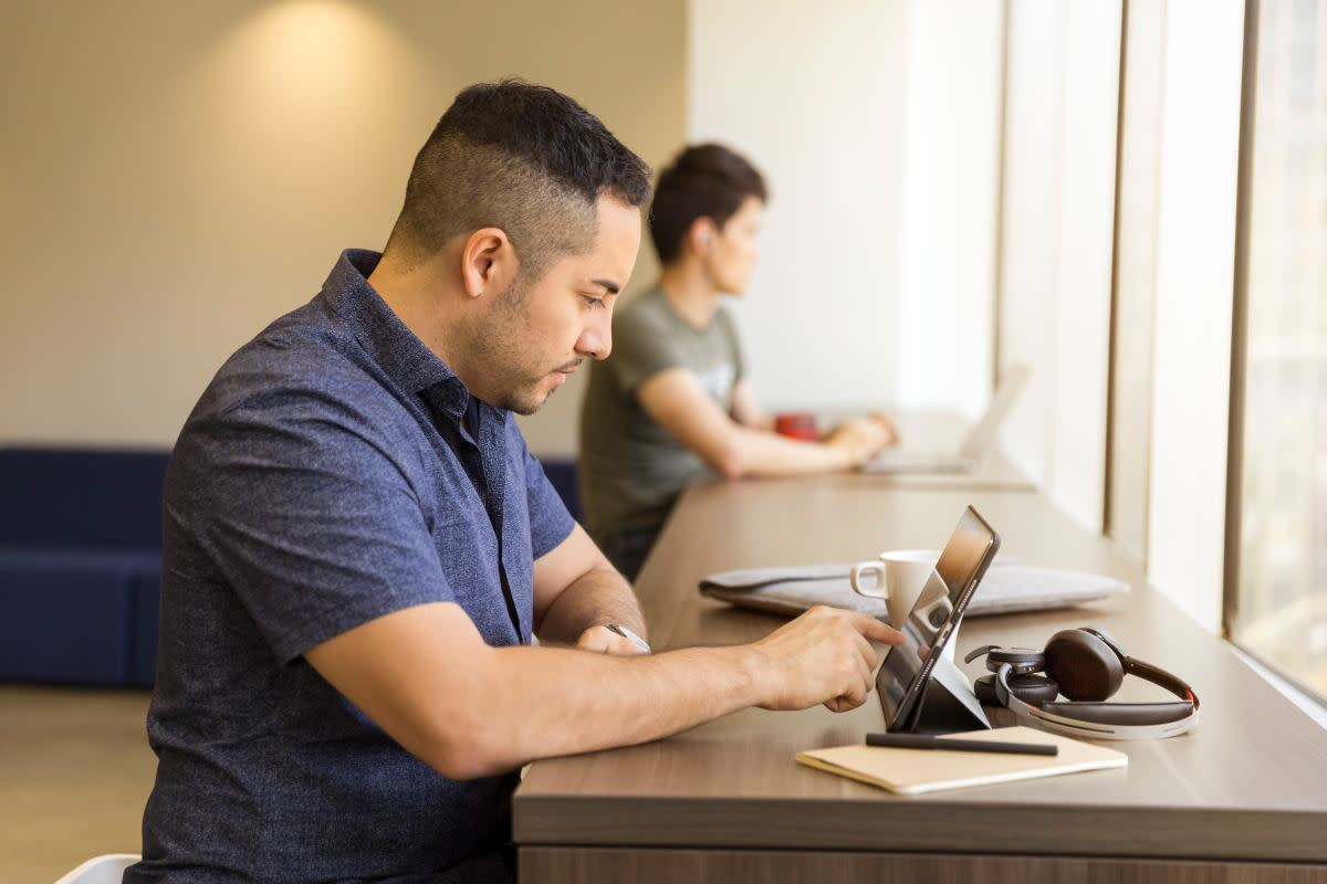 Salesperson with tablet using triggered emails to boost sales