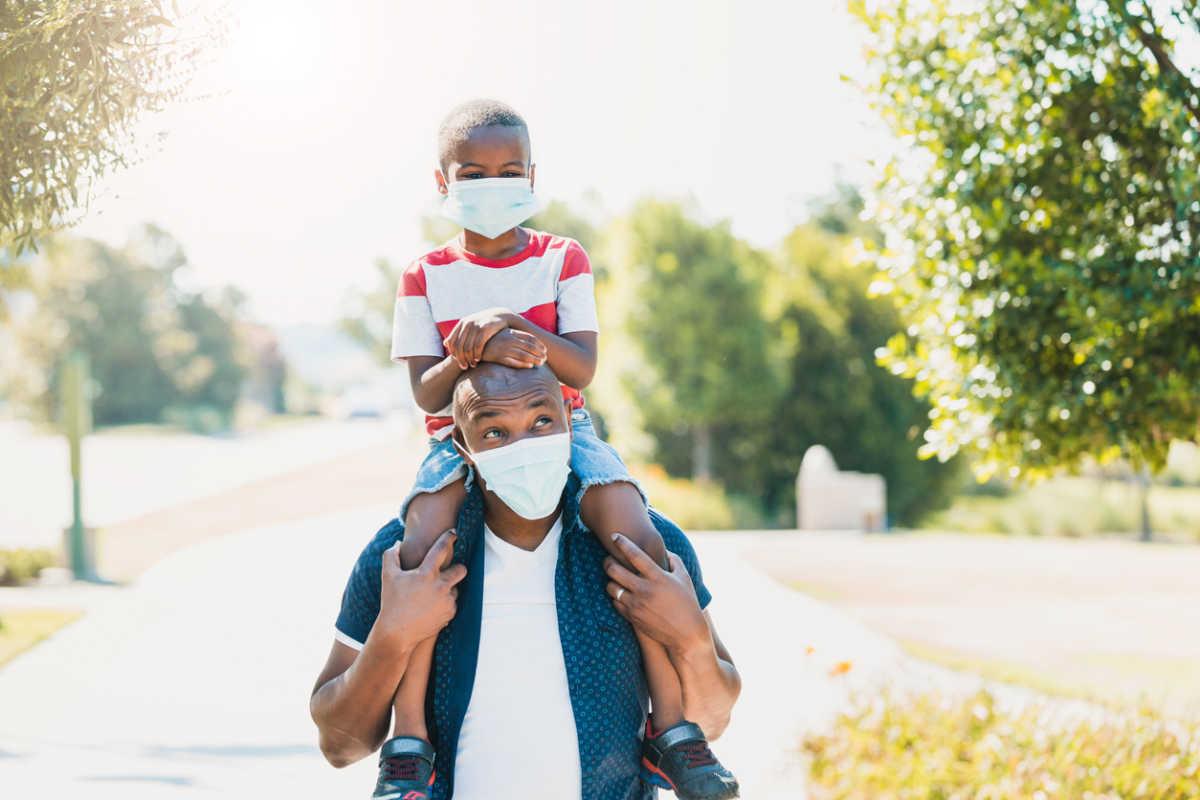 Dad gives son piggy back ride; both wear masks