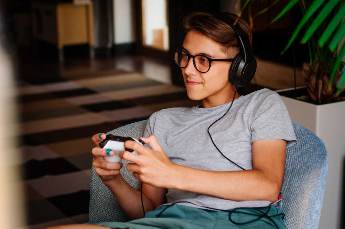 Smiling teenager boy in glasses and headphones playing game console