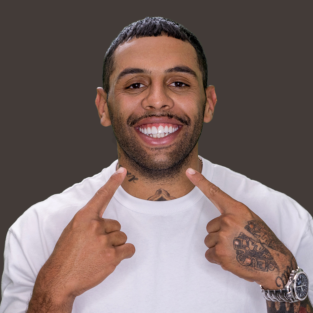 Josh Addo-Carr rugby league footballer pointing to his porcelain veneers smile in white shirt with watch.