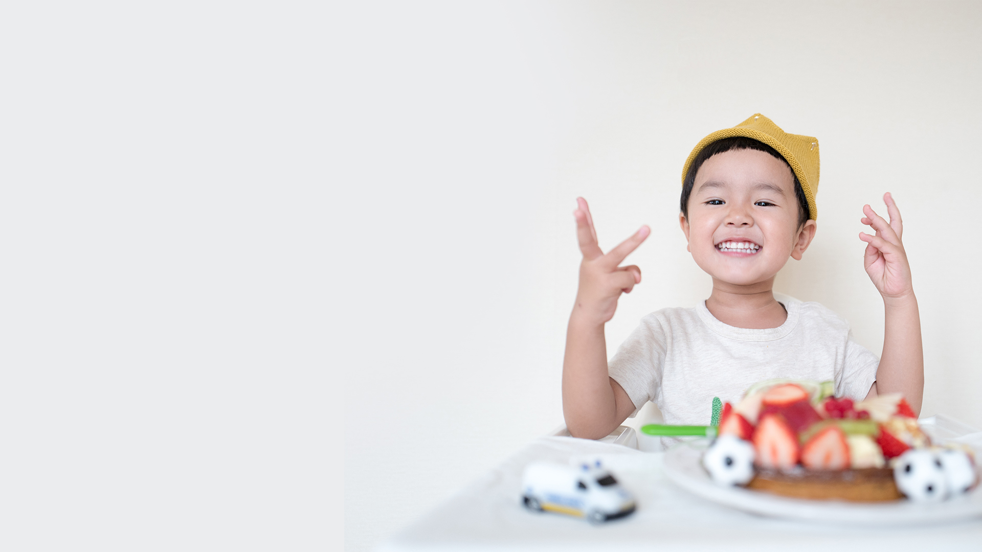 Child with cake and toys smiling.