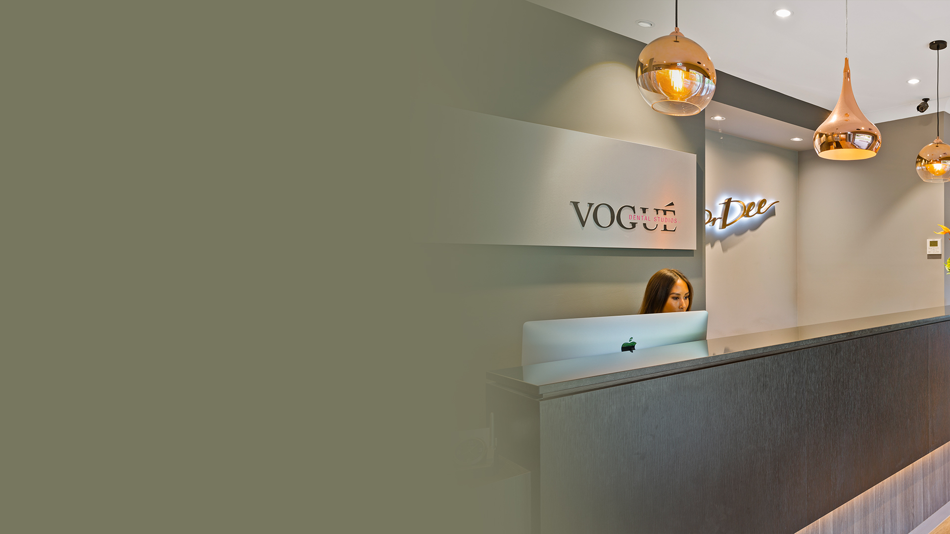 Vogue Dental Studios reception desk with rose gold pendant lights.