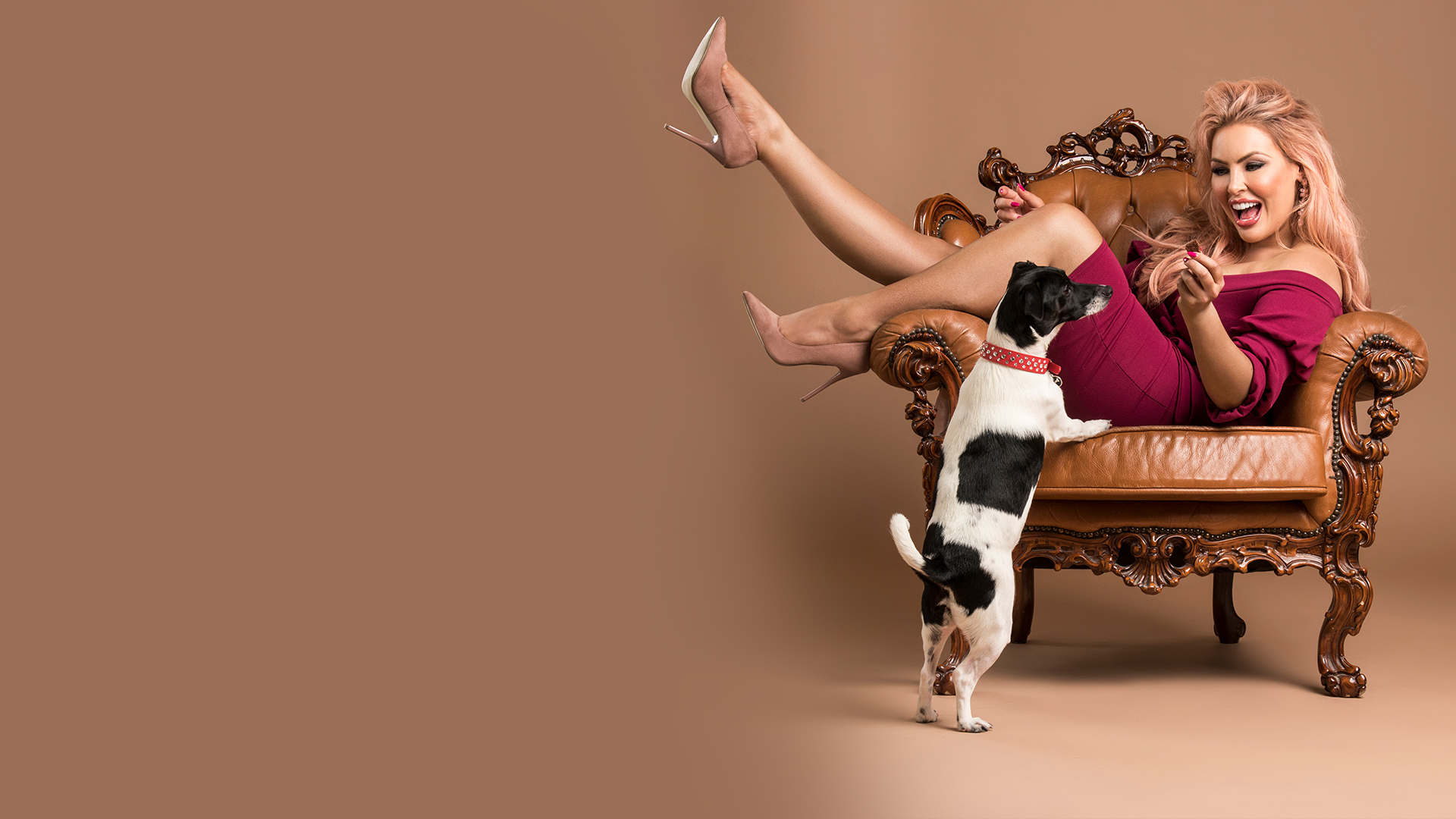 Sarah Roza lying in brown antique armchair playing with her dog.
