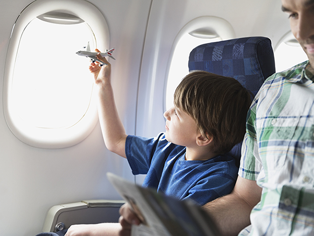 A boy plays with his toy plane sitting in the window seat of a plane.