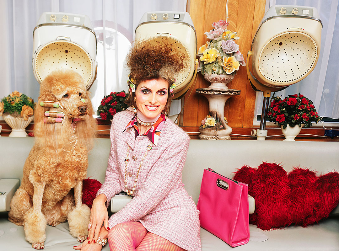 Swoop | a woman wearing a pink dress that just finished with a shopping spree and spa day with her brown poodle, that has their hair styled as well. Text