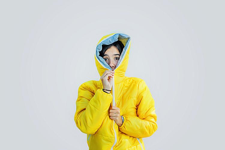 women in a yellow jacket with it zipped up all the way