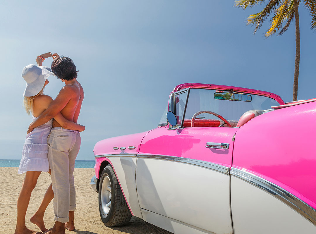 Swoop | a man and a woman by the beach hugging under clear blue skies with a vintage car beside them in Cancun. Text
