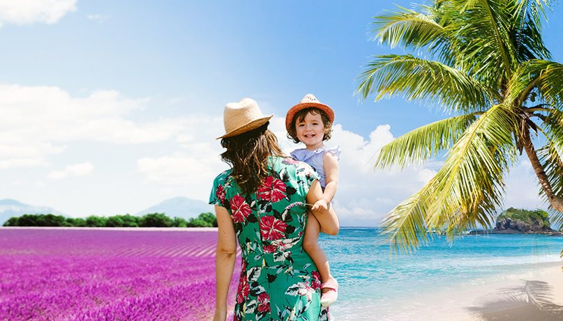 A mother walks on the beach with her child in her arms while the background fades into a sea of flowers.