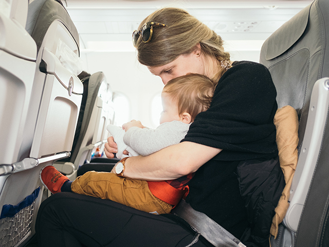 A mother is sitting in the aisle seat with her small child on her lap.