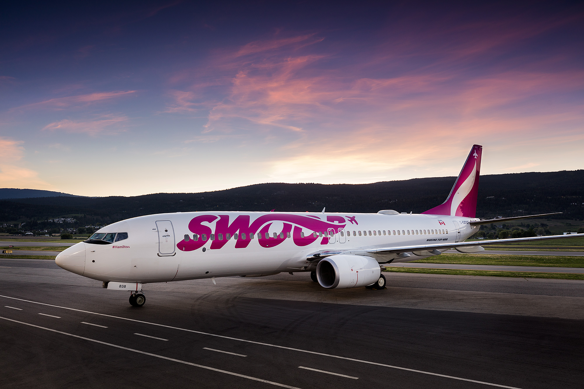 side of swoop livery with a sunrise in the background at halifax airport
