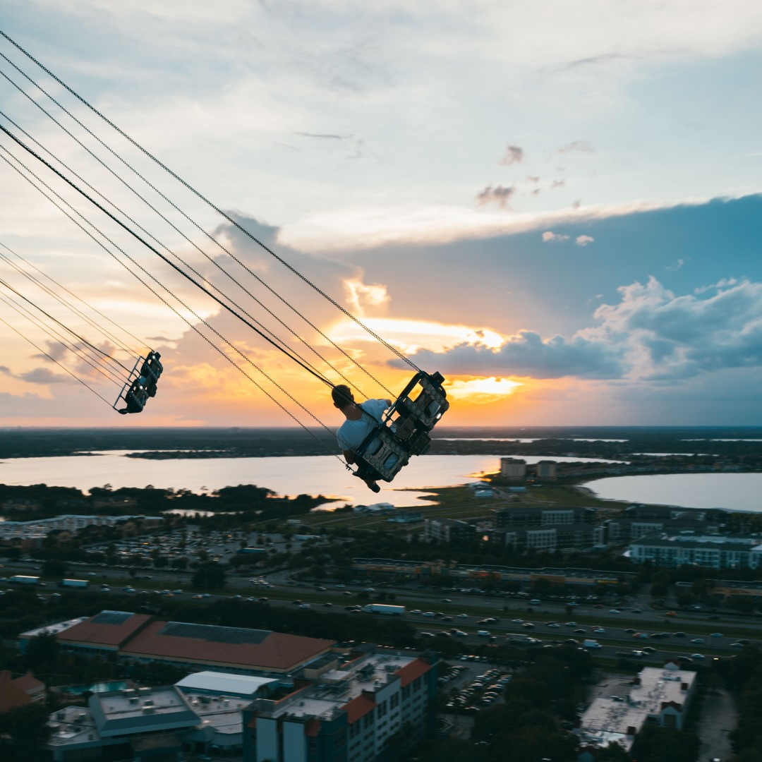 Swoop | a person riding on the starflyer in orlando florida in the sky during sunset