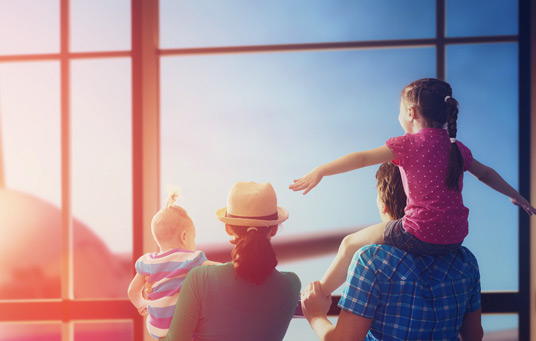 A family is looking outside a window at an airplane. The daughter is on the fathers shoulders with her arms out pretending to be an airplane.