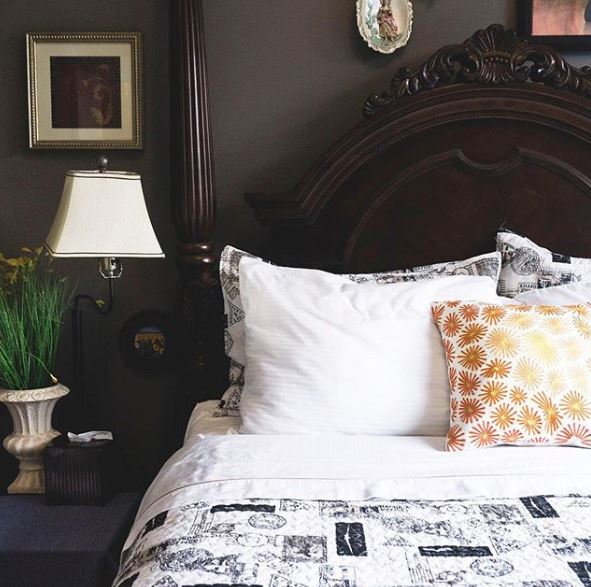 Image of nicely made bed with white, blue and gold bed sheets and pillows.