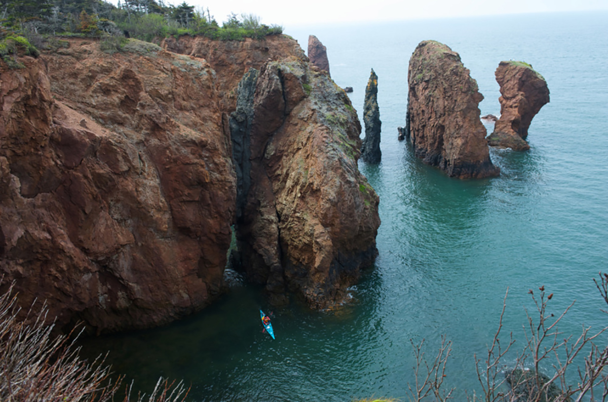 image is cliff in the water with a person kayaking below.