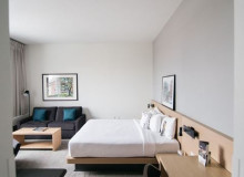 image of hotel room with a bed, couch and desk in it