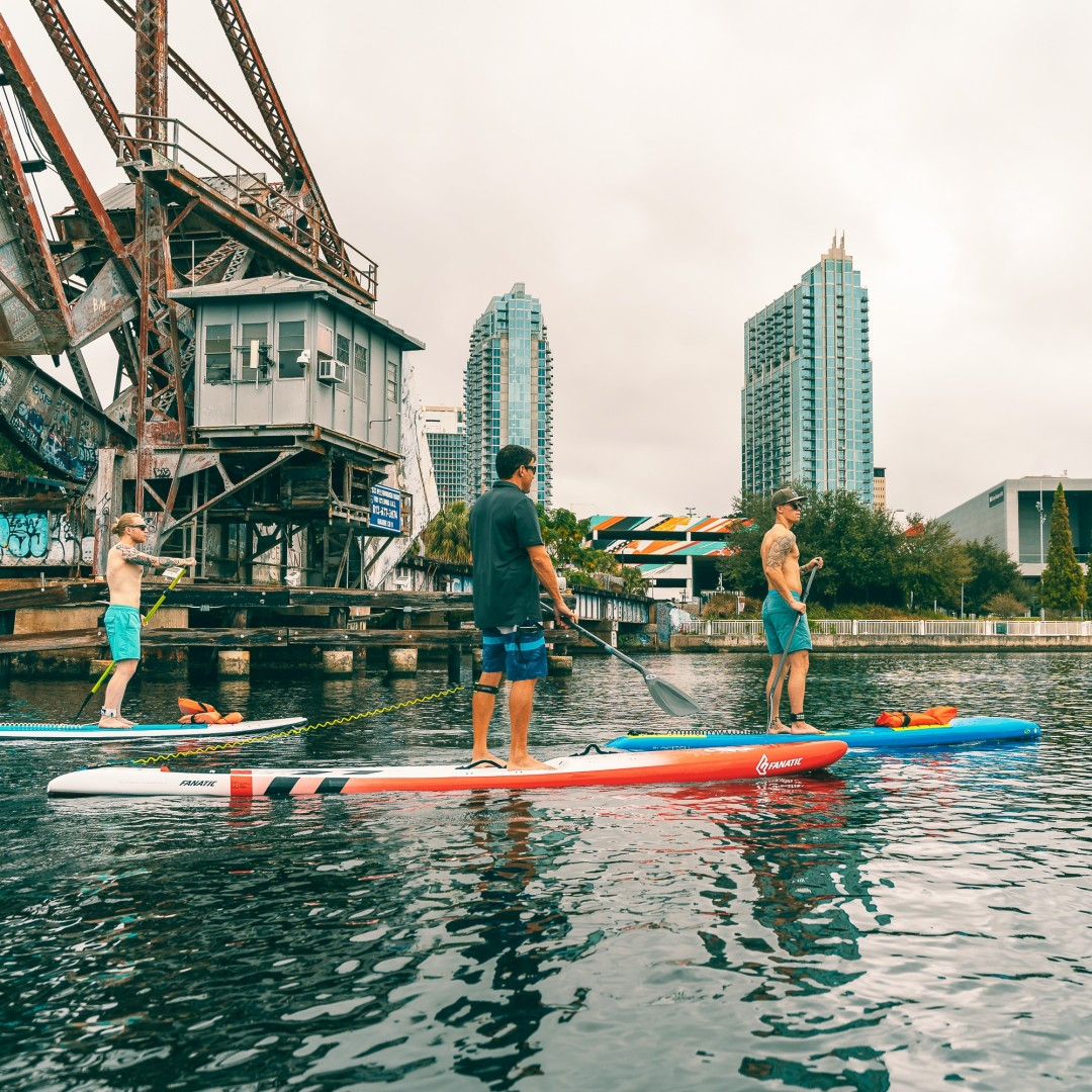 Swoop | three men paddle boarding on the river in Tampa, Florida