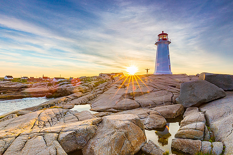 image of peggy's cove lighthouse with the sun shining through.