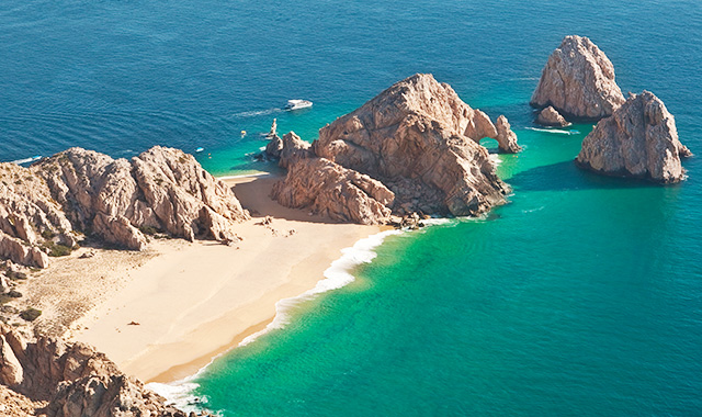 Swoop | a picture of the lover's beach surrounded by clear indigo waters with rock formations in Los Cabo
