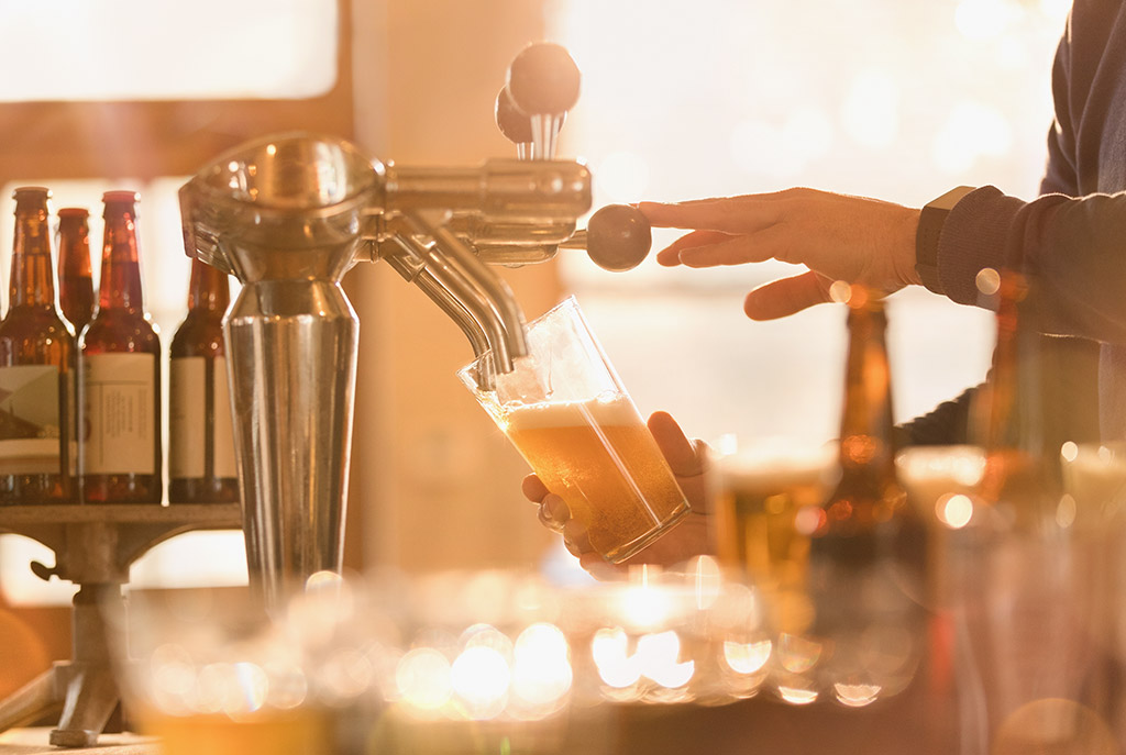 Swoop | picture of someone pouring beer out of a tap in a Hamilton brewery