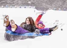 Swoop | two kids snow tubing down the Sunridge ski area in Edmonton during the winter time
