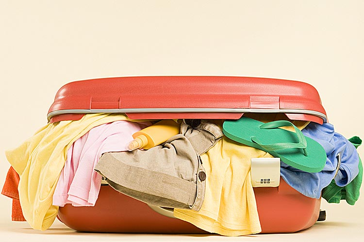 An orange suitcase overflowing with messy clothes.