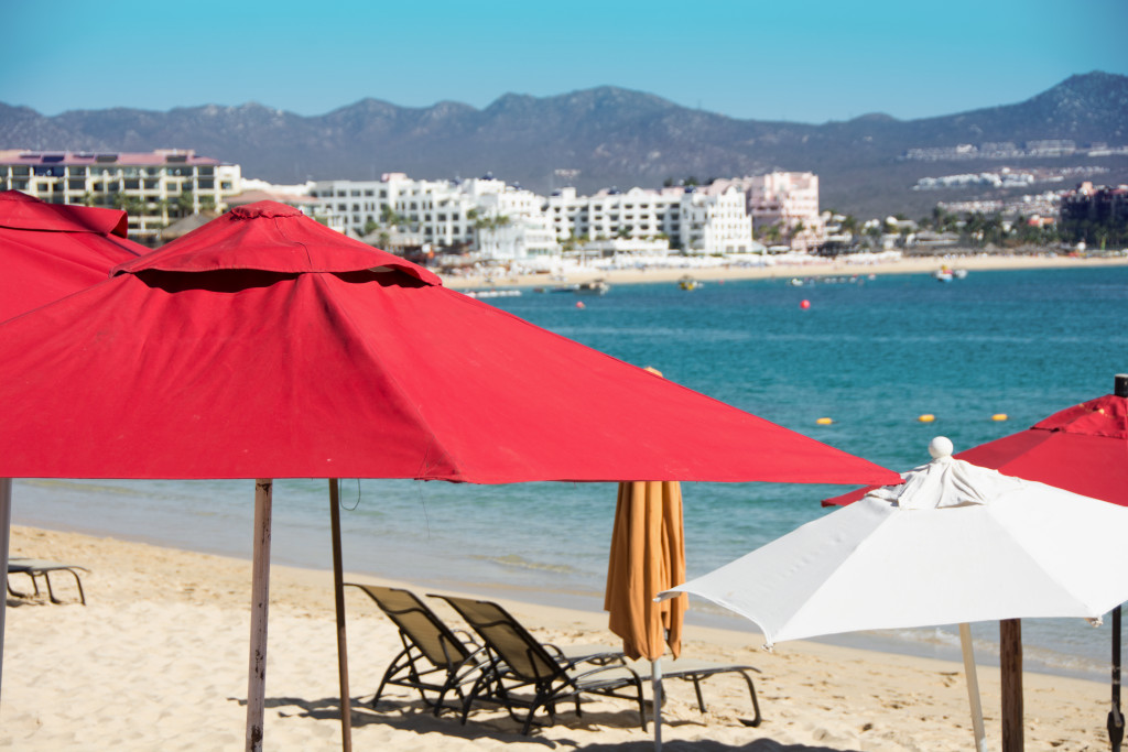 Swoop | a picture of the beach in Los Cabos, Mexico with red umbrellas