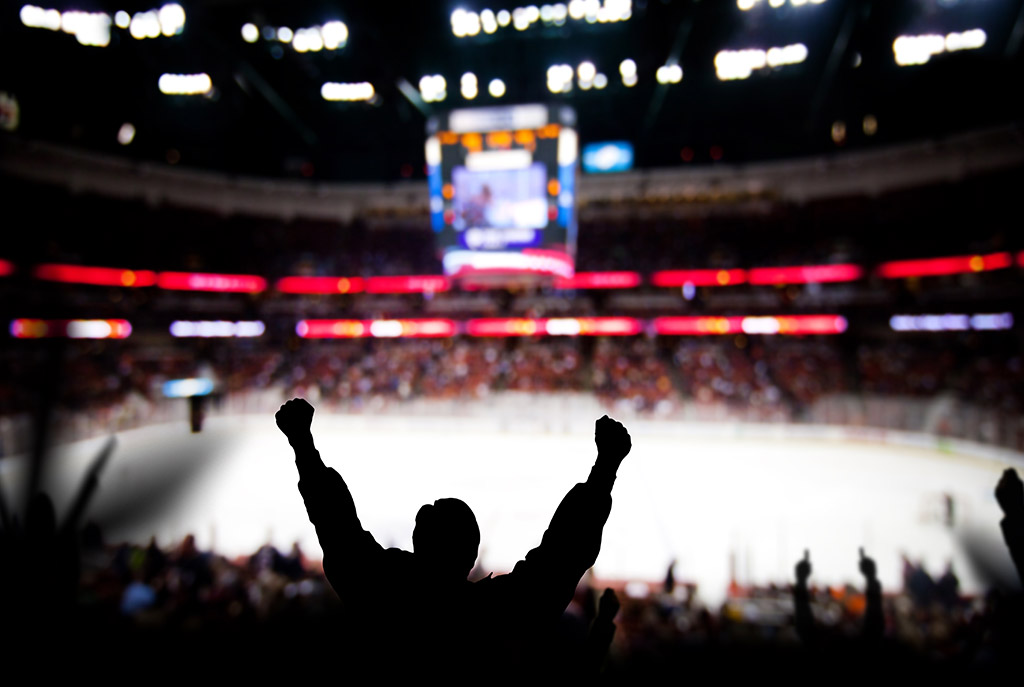 Swoop | a picture of the hockey arena inside the Rogers Place in Edmonton, the shadows of a hockey fan with their hands up cheering