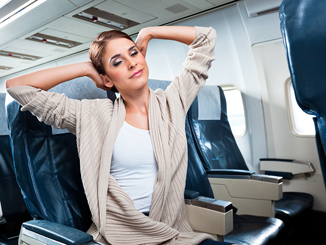 A woman stretches in her aisle seat.