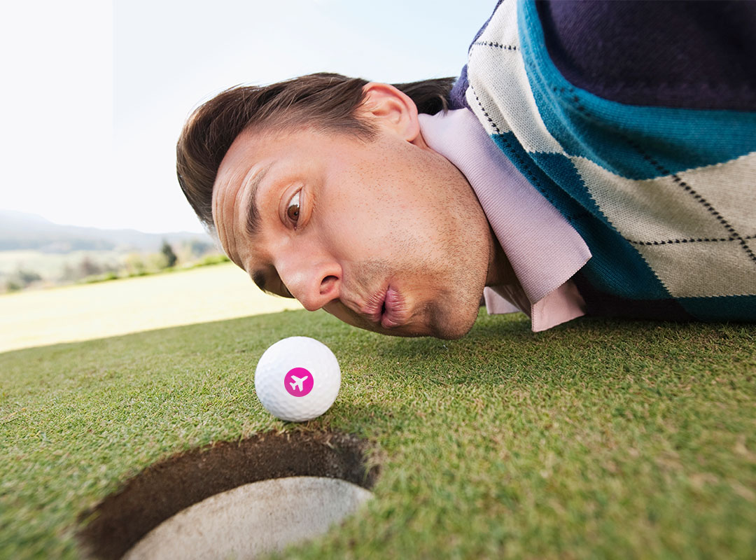 Swoop | a man on a golf course trying to blow a swoop golf ball into the hole. Text