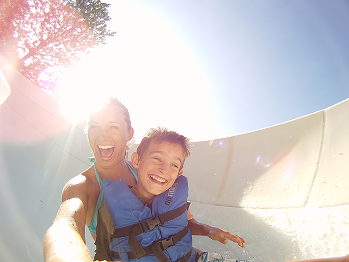 mom and son wearing life jacket smile as they go down a slide