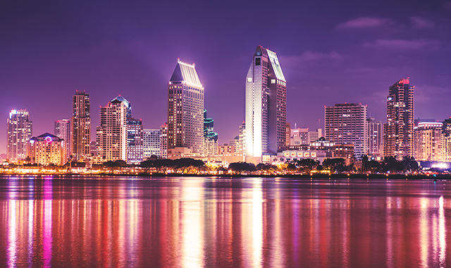 Swoop | A night view of the San Diego skyline with vibrant magenta colours