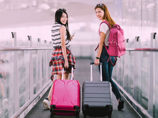 Two young friends pulling their suitcases at the airport, ready to head on a weekend vacation.