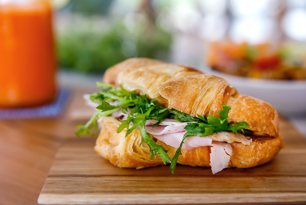 Swoop | a picture of a croissant sandwich stuffed with ham and arugula in Abbotsford