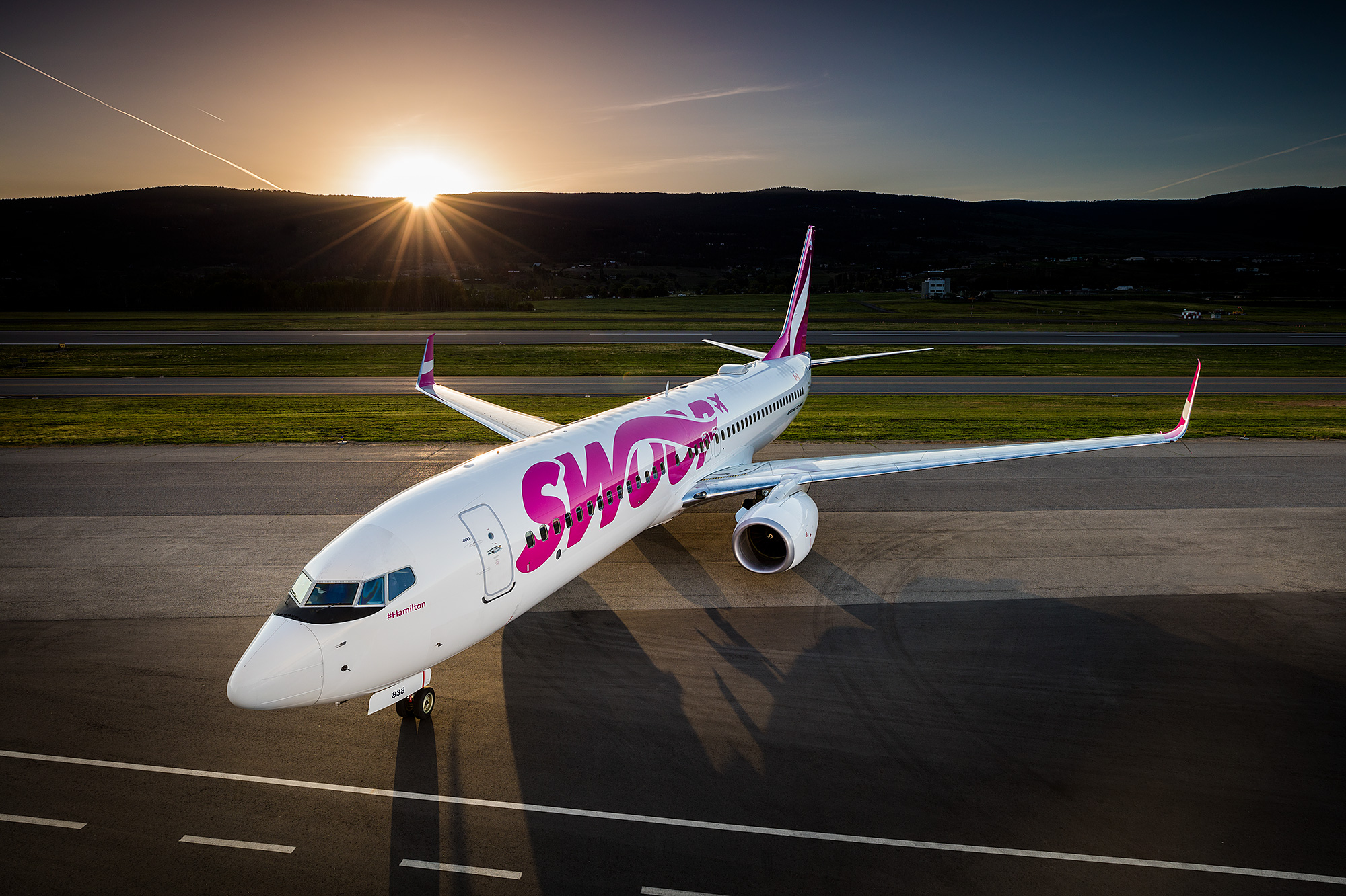 side of swoop livery with a sunset in the background at kelowna airport
